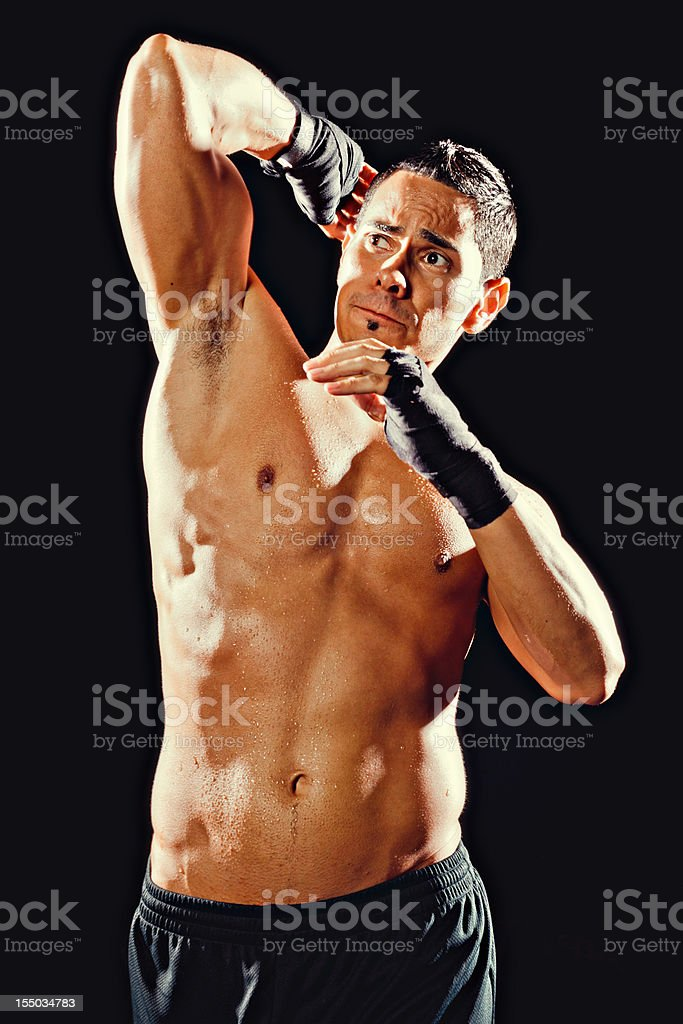 Fit male fighter throwing a high elbow royalty-free stock photo