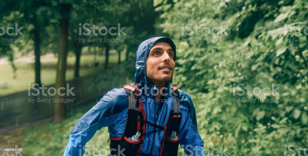 Fit male jogger day training in the rain for cross country forest trail race in a nature park stock photo