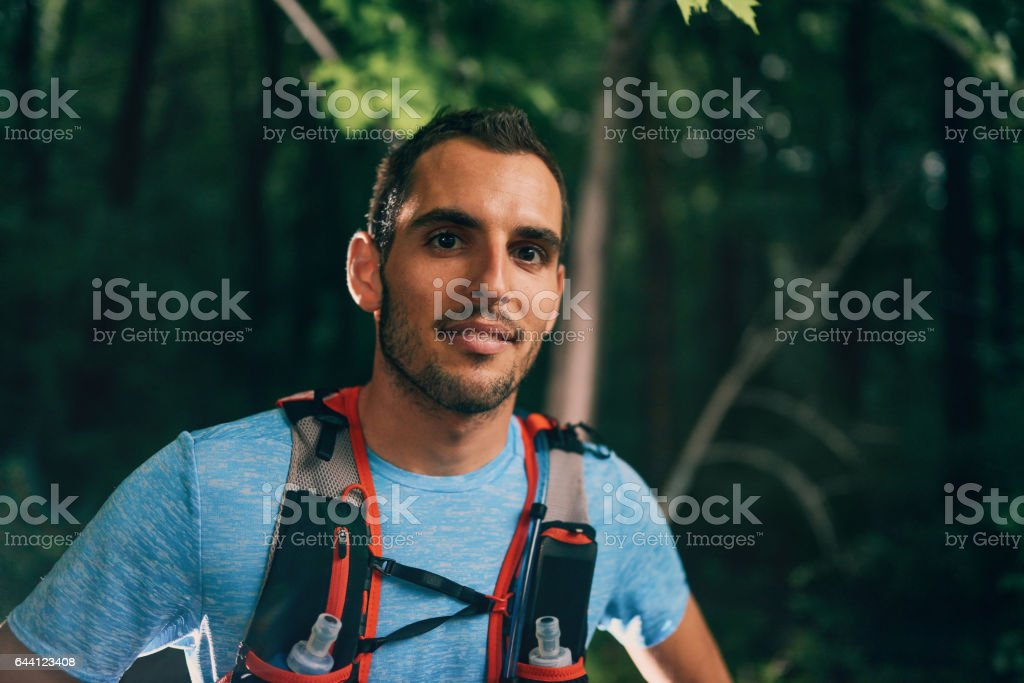 Fit male jogger resting during day training for cross country forest trail race in a nature park stock photo