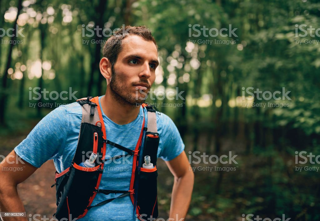 Fit male jogger rests during day jogging for cross country forest trail race in a nature park stock photo