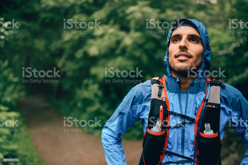 Fit male jogger rests during day training for cross country forest trail race in a nature park stock photo