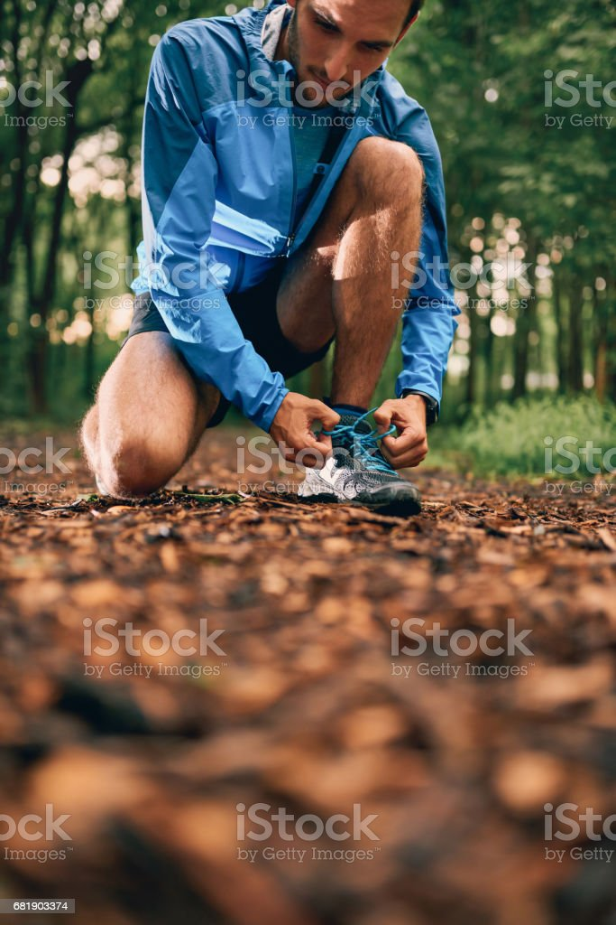 Fit male jogger ties shoes while day training for cross country forest trail race in a nature park stock photo