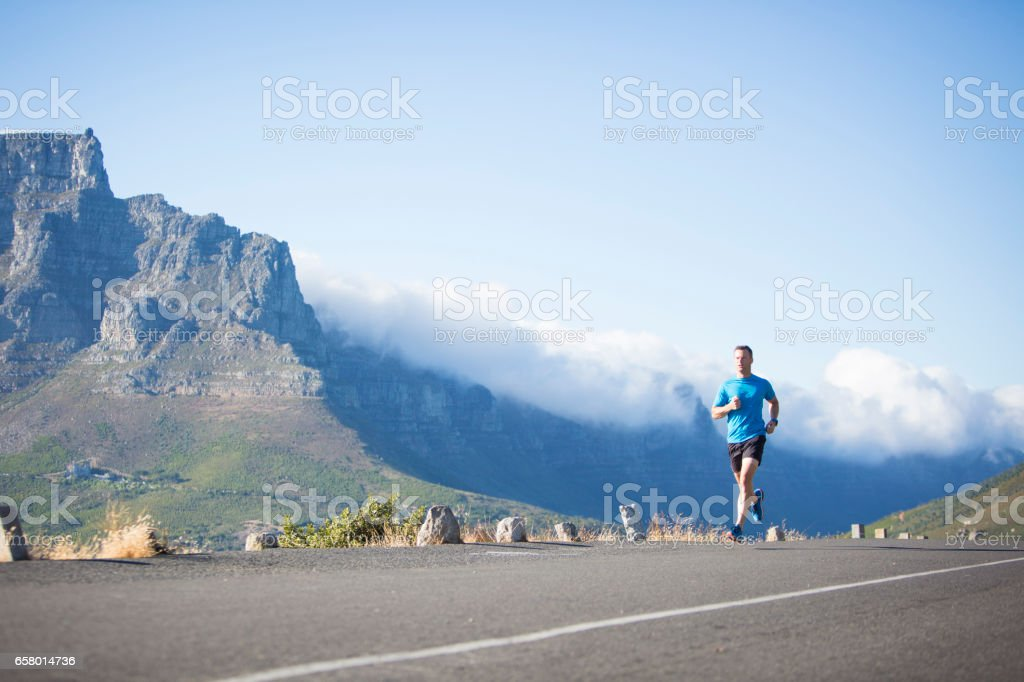 Fit male running along a road stock photo