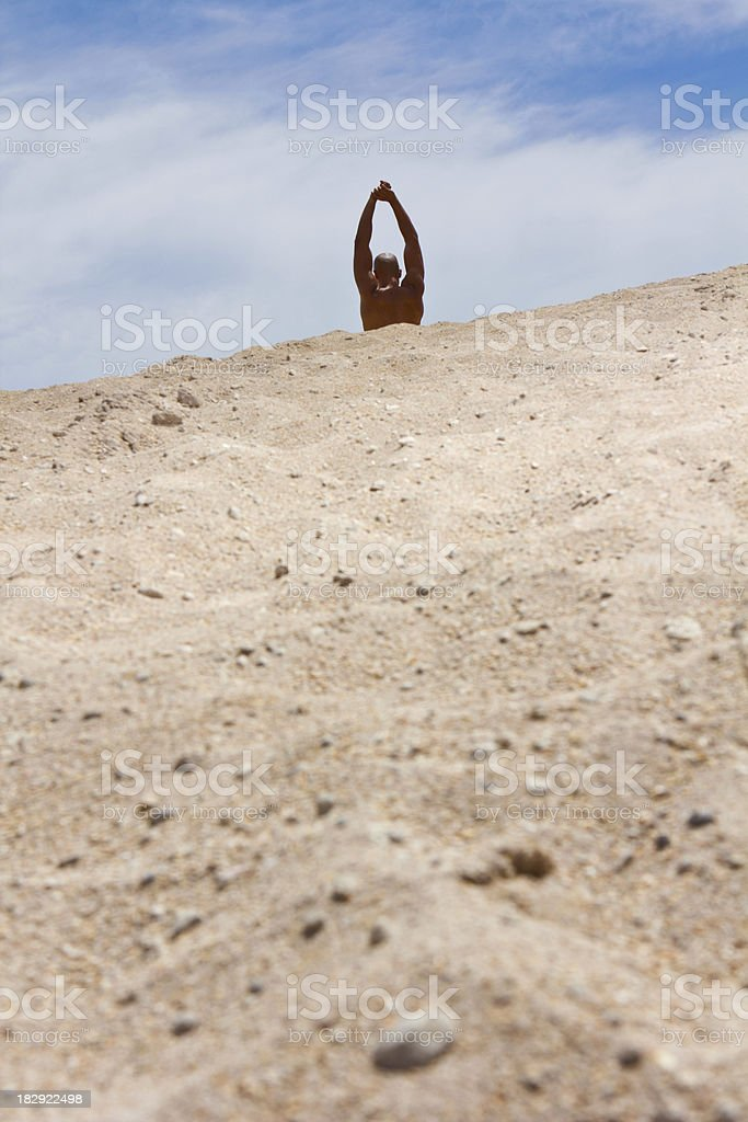 Fit male stretching behind sand royalty-free stock photo