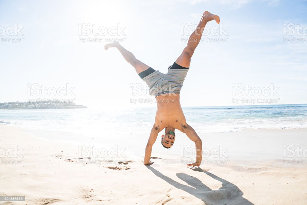 Fit man doing a cartwheel at the beach stock photo