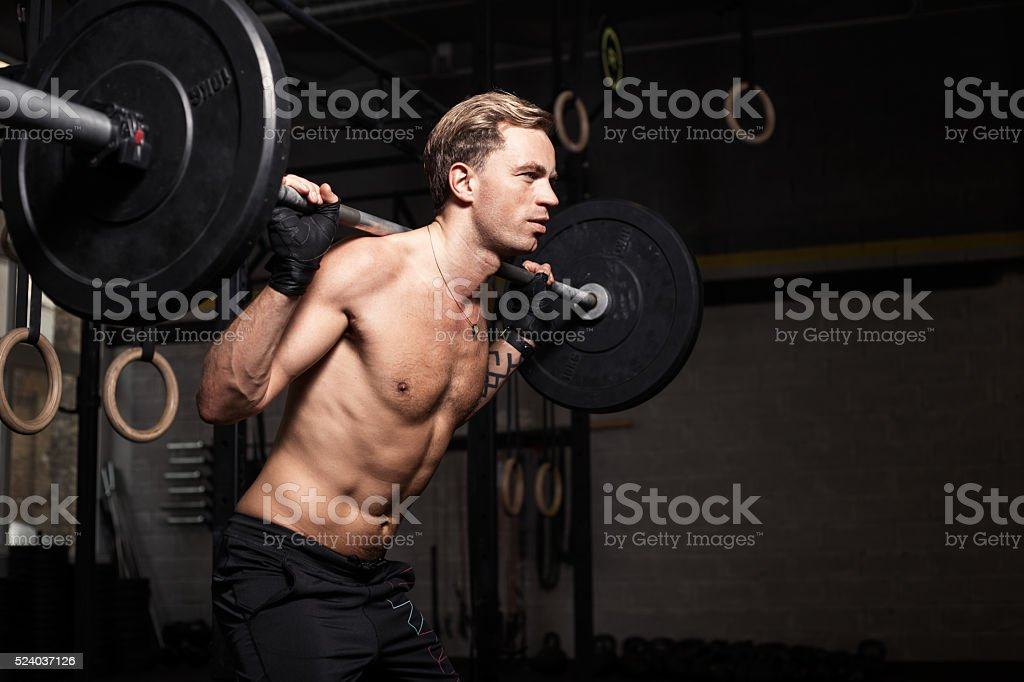 Fit man doing squads with weights on his shoulders stock photo