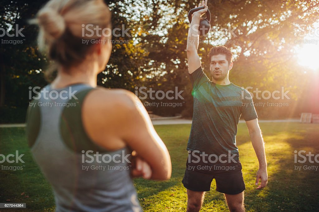 Fit man exercising with female trainer in park stock photo
