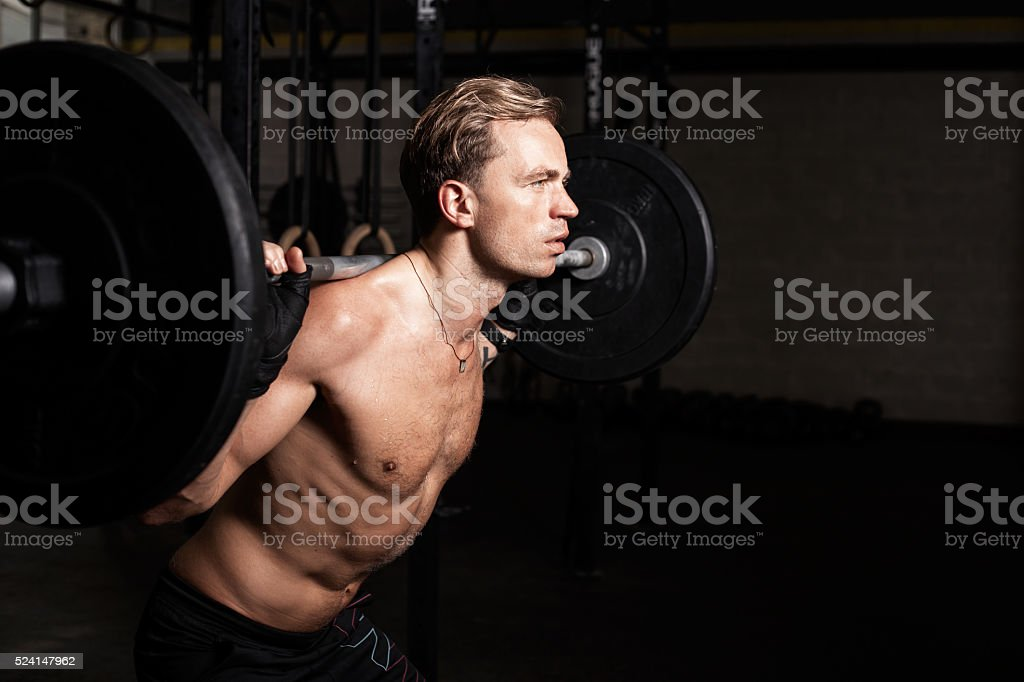 Fit man in gym lifting weights stock photo