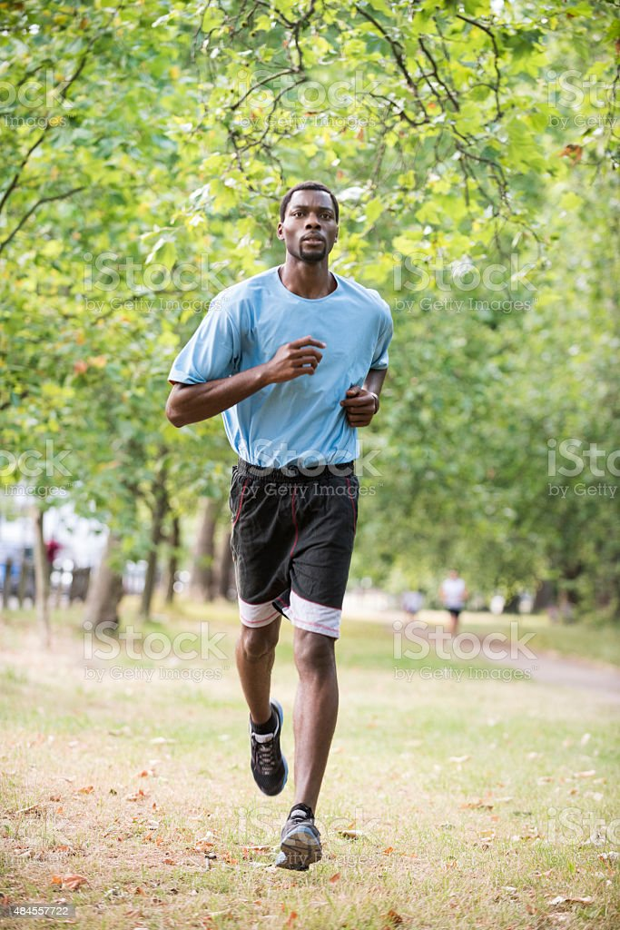 Fit man jogging on country road stock photo