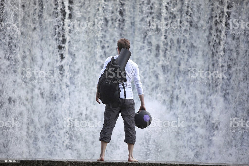Fit man  on footbridge at the waterfall watching water stock photo