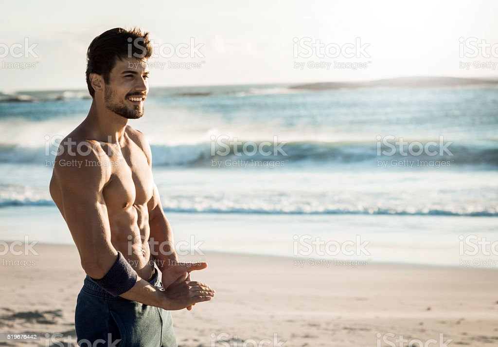 fit man relaxing on the beach stock photo