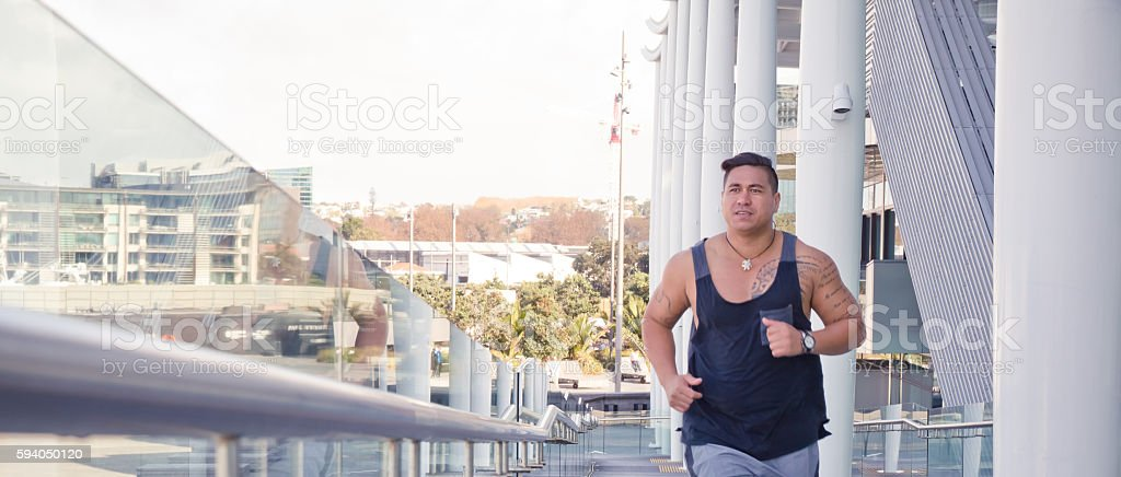 Fit man running in urban Auckland city buildings Pacific Islander stock photo