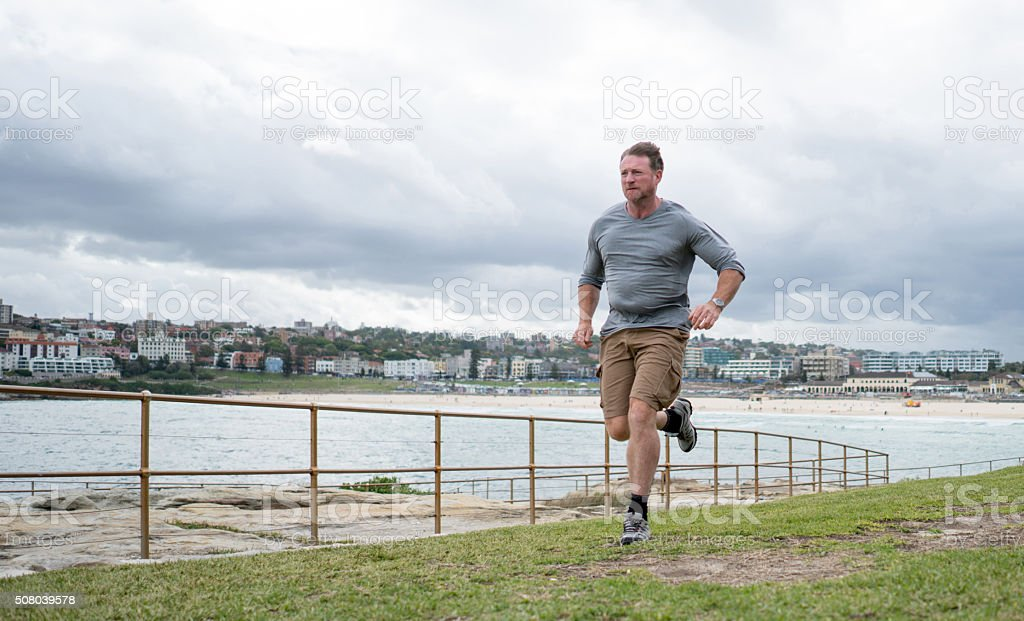 Fit man running outdoors stock photo