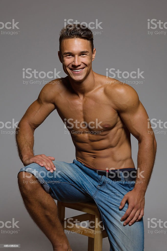 Fit Man Sitting On A Wooden Stool stock photo
