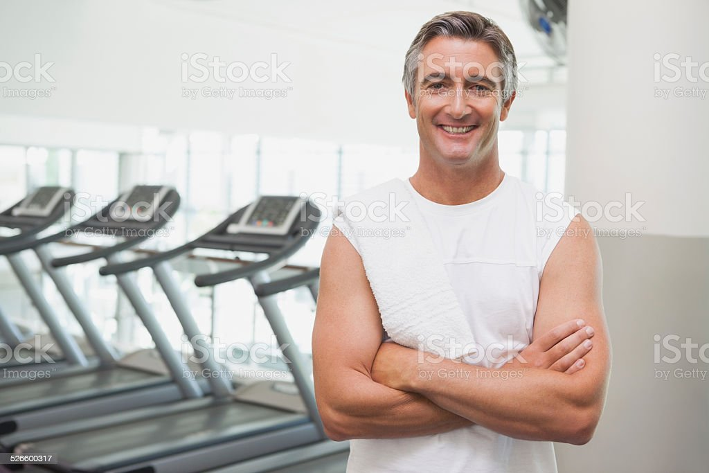 Fit man smiling at camera beside treadmills stock photo