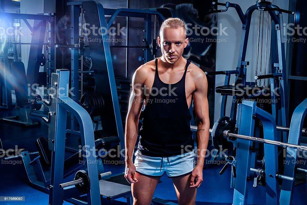 Fit man standing in the gym stock photo