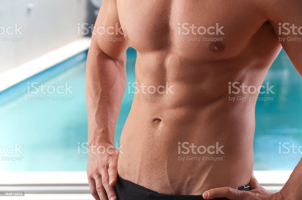 Fit man's chest with swimming pool in the background royalty-free stock photo