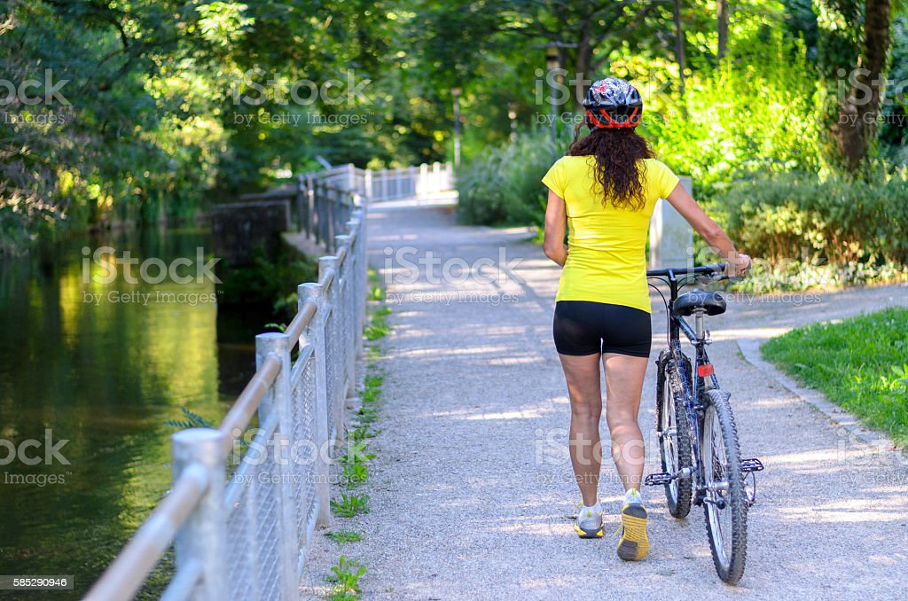 Fit muscular woman wheeling her bicycle outdoors stock photo
