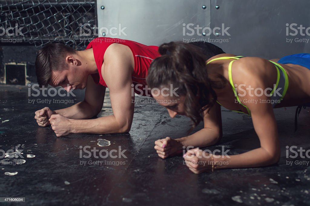 fit sportive man and woman doing plank core exercise training stock photo