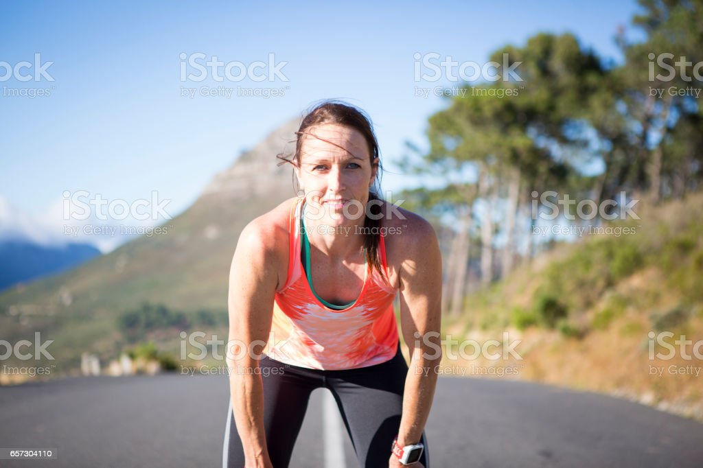 Fit sportswoman stops for a rest at the top of the hill stock photo