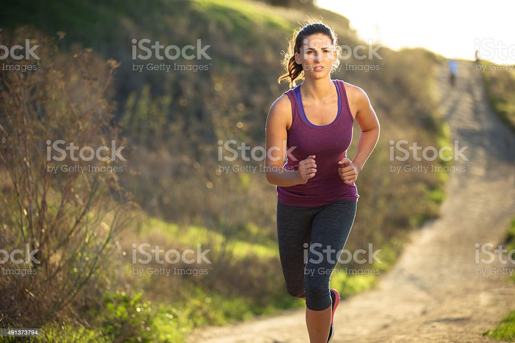 Fit toned woman jogging running outdoors morning park nature hike stock photo
