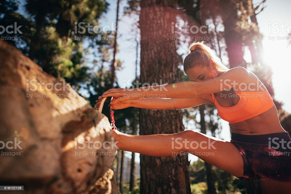 Fit woman athlete stretching leg on a nature trail run stock photo