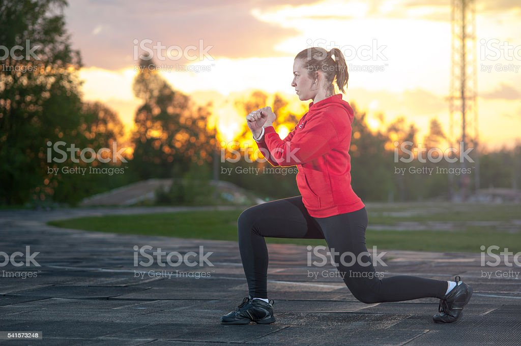Fit woman doing frontal lunges outdoors stock photo