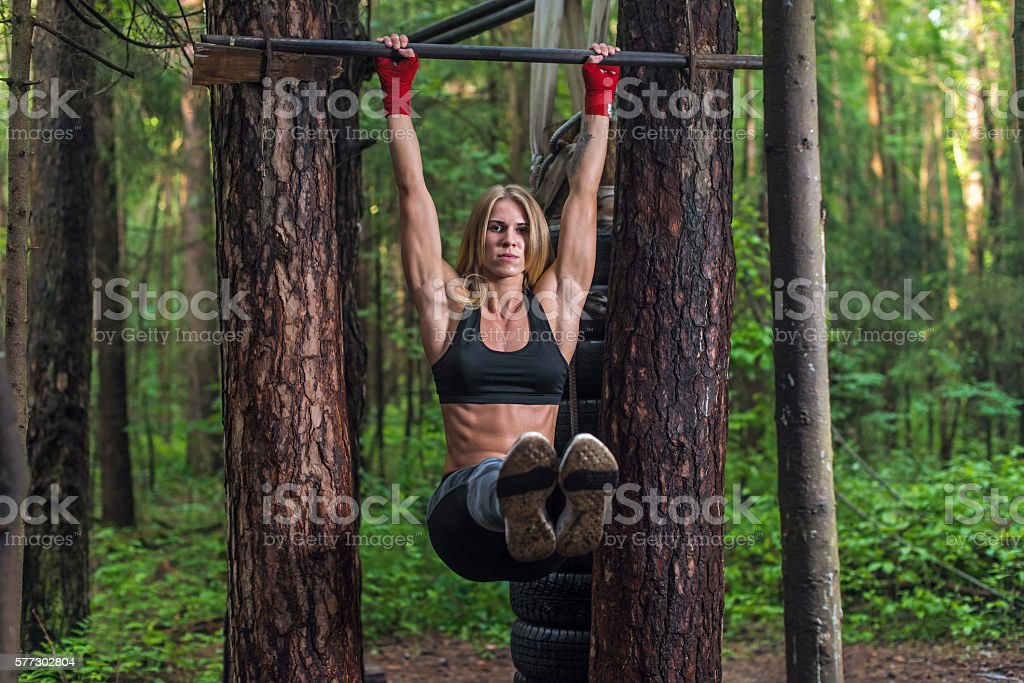 Fit woman doing hanging leg lifts abs muscles exercise on stock photo