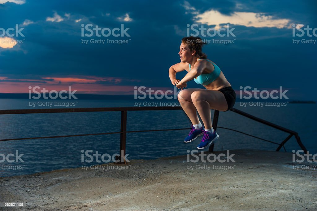 Fit woman doing plyometric exercises on pier stock photo