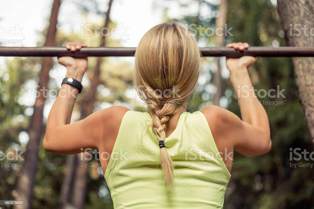 Fit woman doing pull-ups stock photo