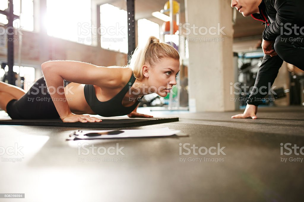 Fit woman doing push ups with personal trainer in gym stock photo