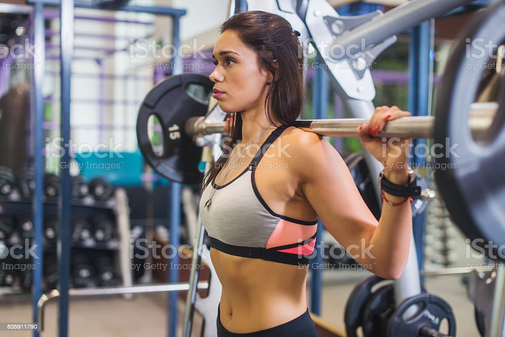 Fit woman doing shoulder press exercise with a weight bar stock photo