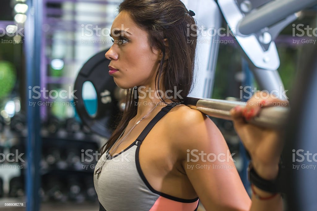 Fit woman doing squats with a barbell in Smith machine. stock photo