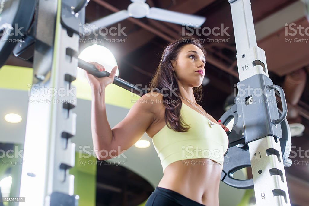 Fit woman doing squats with the barbell Smith machine in stock photo