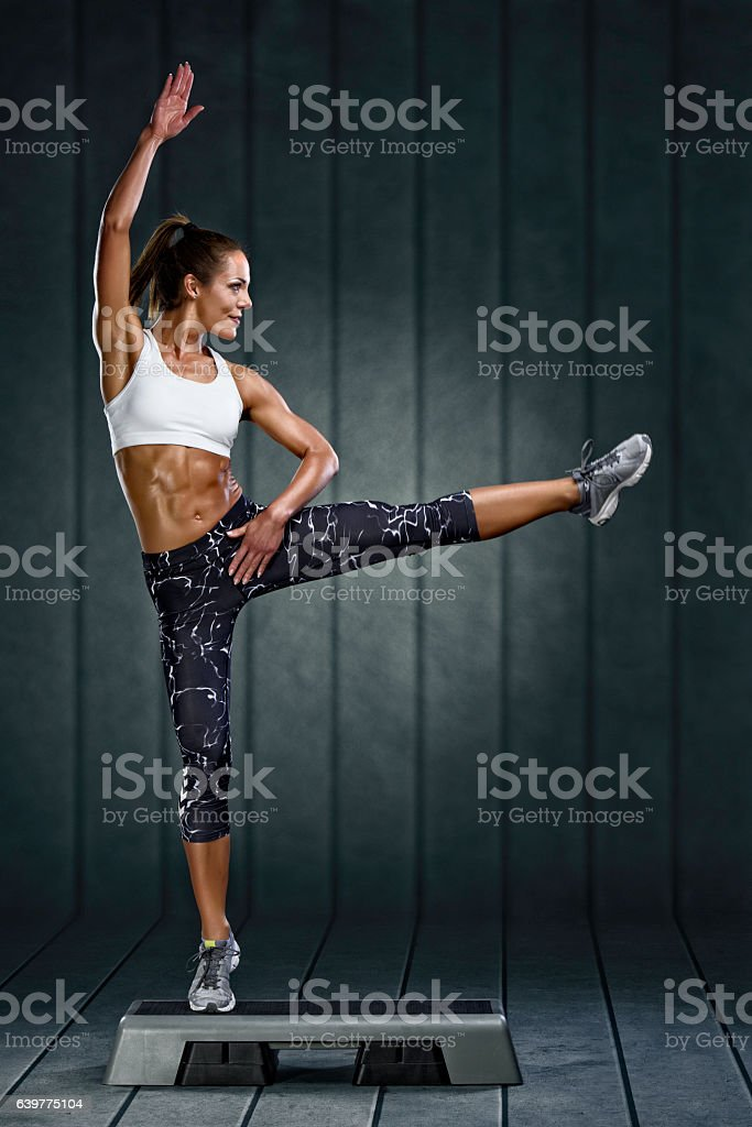 Fit woman doing step aerobics stock photo