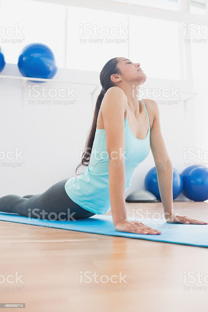 Fit woman doing the cobra pose in fitness studio stock photo