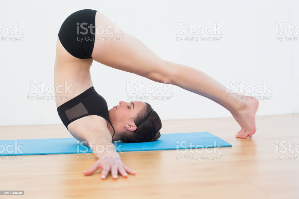 Fit woman doing the plough posture in fitness studio stock photo