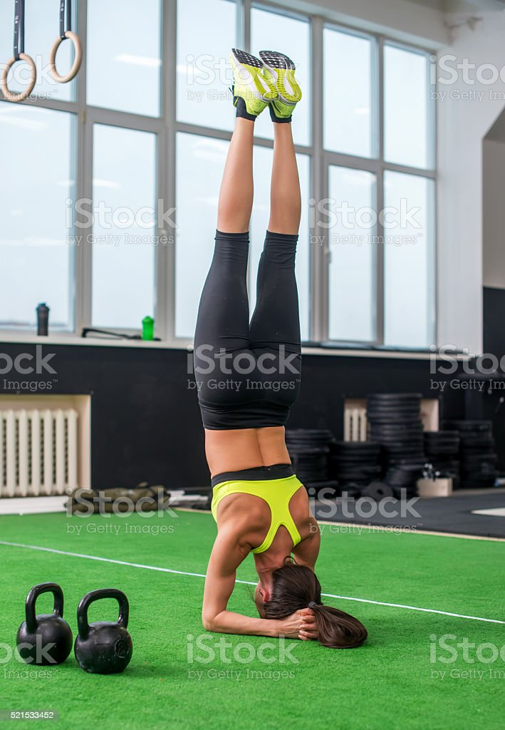 fit woman doing yoga exercise, headstand asana in gym stock photo