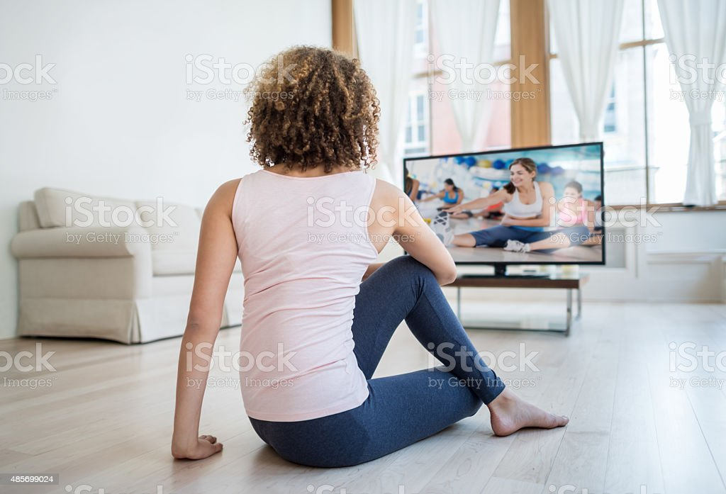 Fit woman exercising at home watching a DVD stock photo