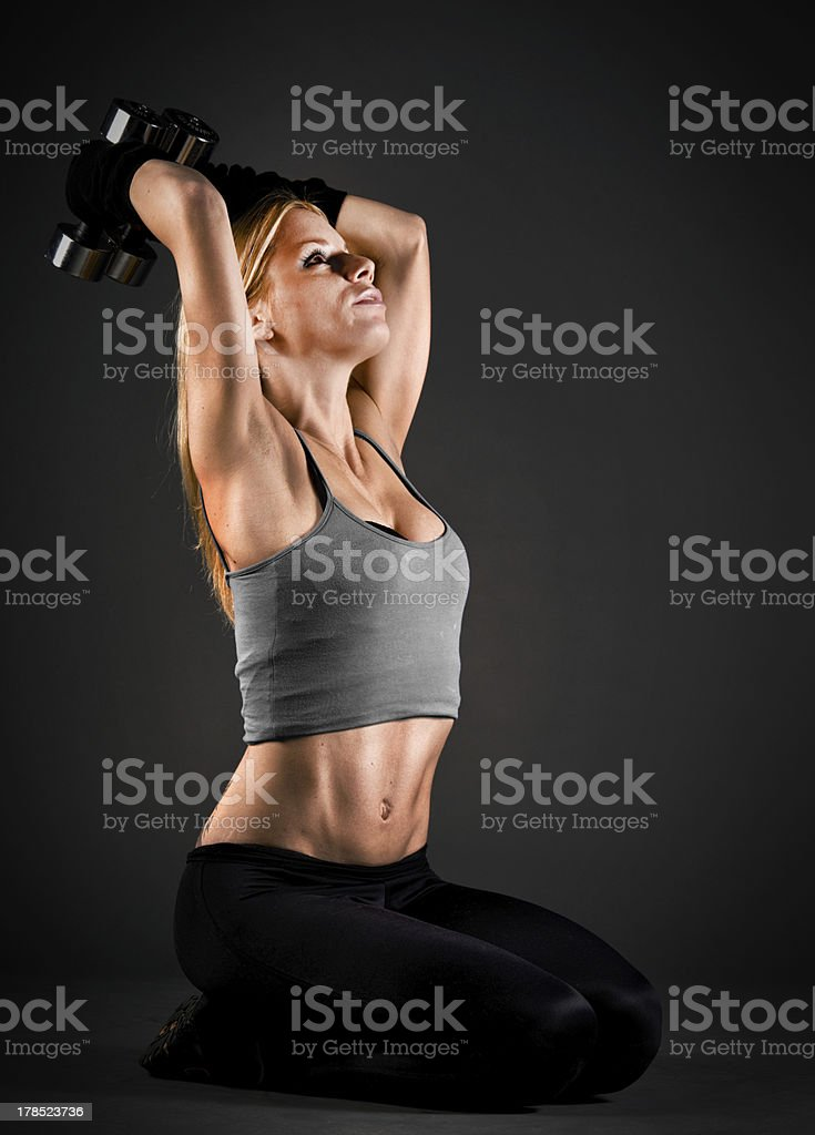 Fit woman exercising with weights over a dark background royalty-free stock photo