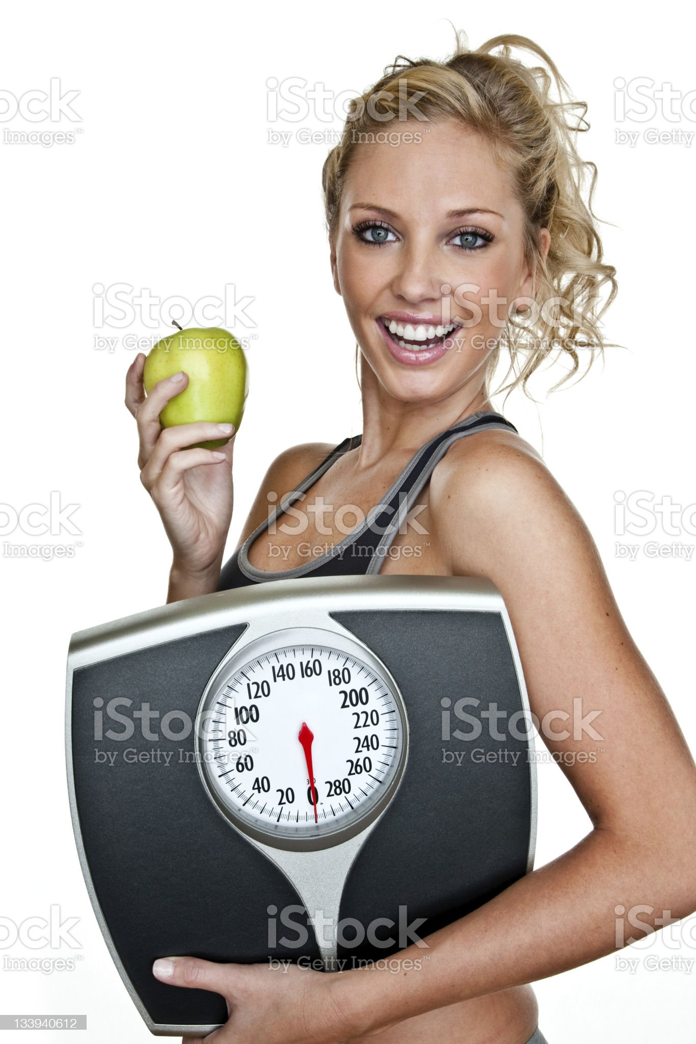 Fit woman holding a scale and apple royalty-free stock photo
