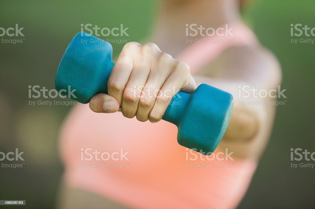 Fit woman holding blue dumbbell in park stock photo
