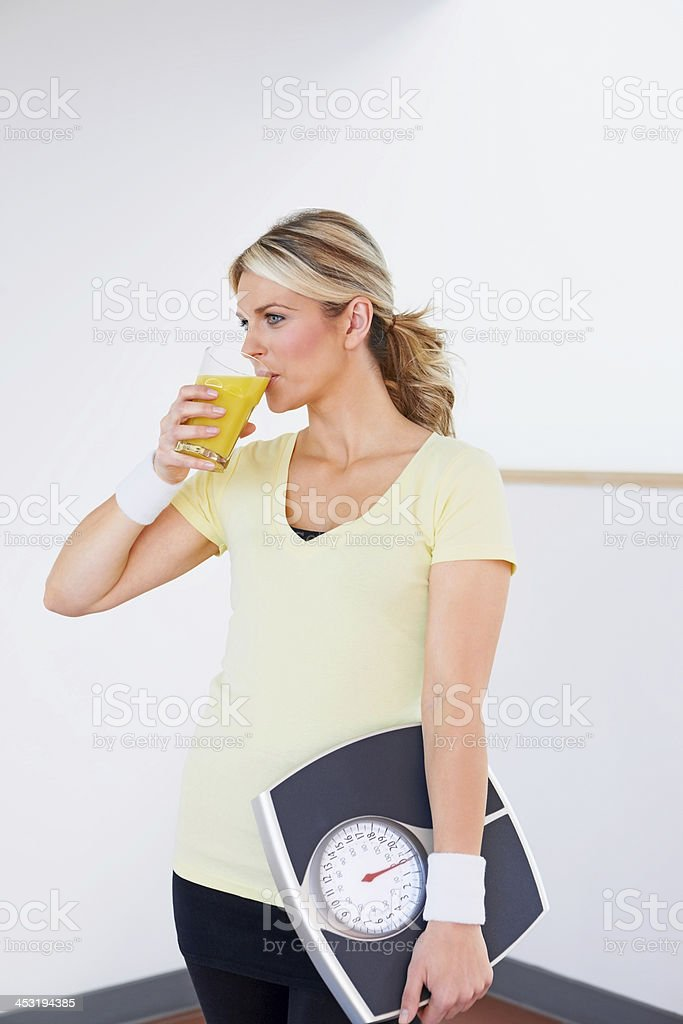 Fit woman holding scales drinking juice royalty-free stock photo
