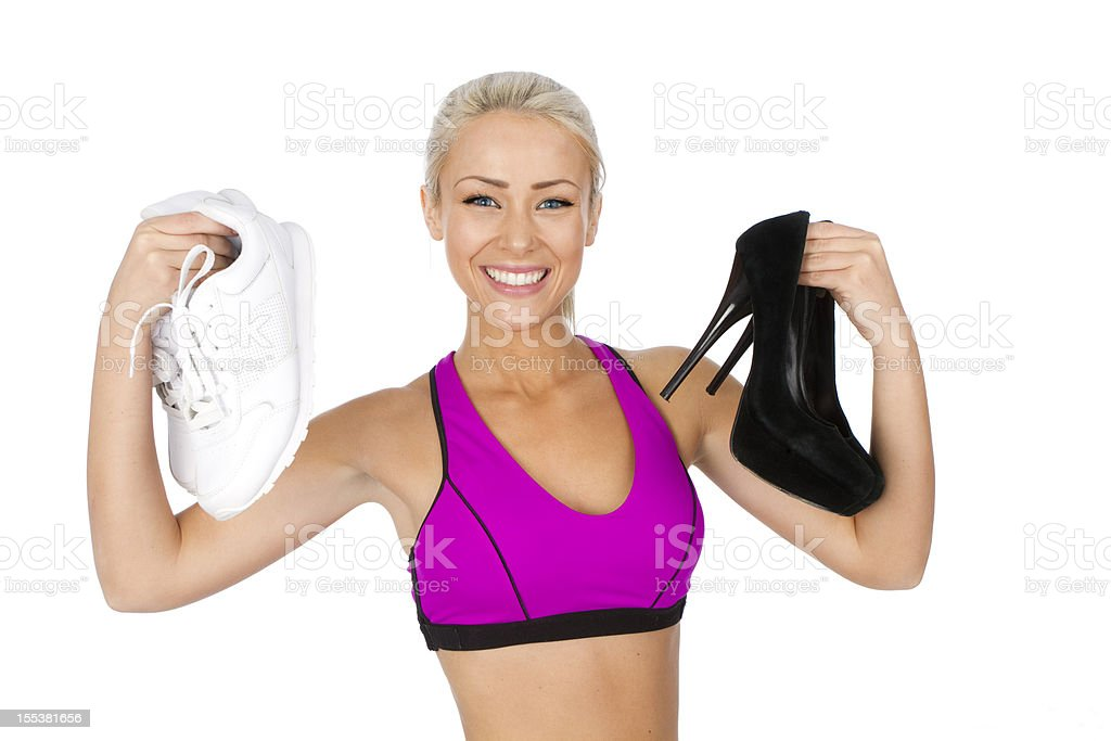 fit woman holding sneakers and high heels royalty-free stock photo