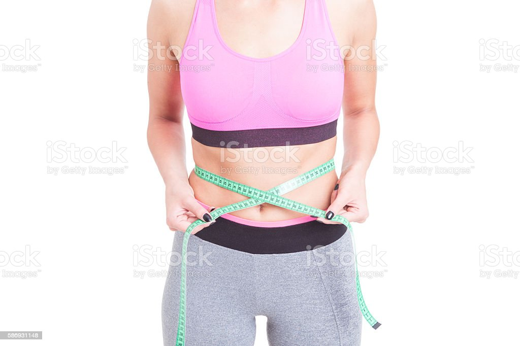 Fit woman holding tape line on waist stock photo