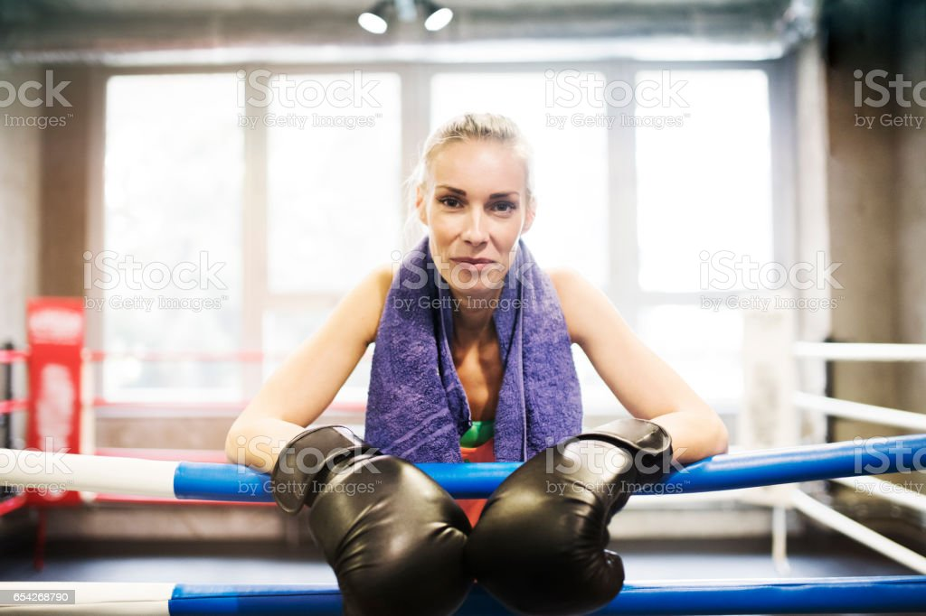Fit woman in gym standing in ring with boxing gloves on . stock photo
