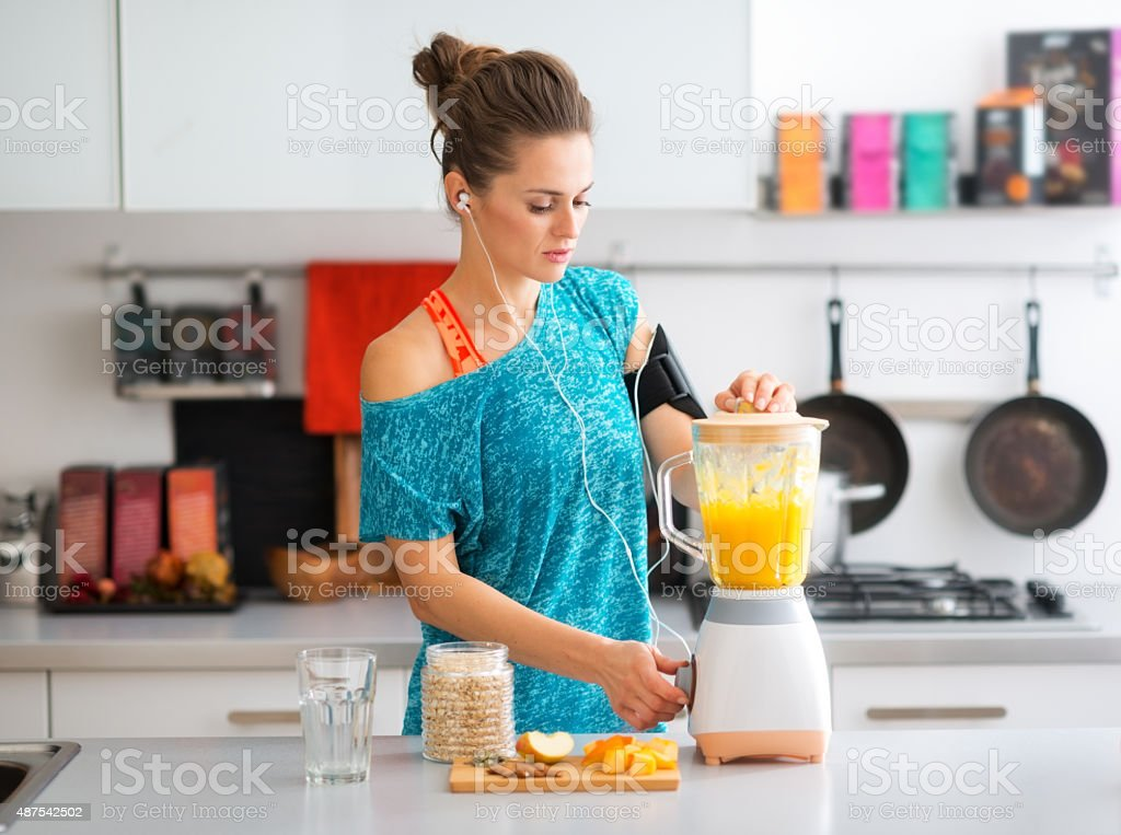 Fit woman in kitchen making a smoothie stock photo