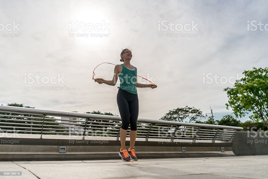 Fit woman jumping rope outdoors stock photo