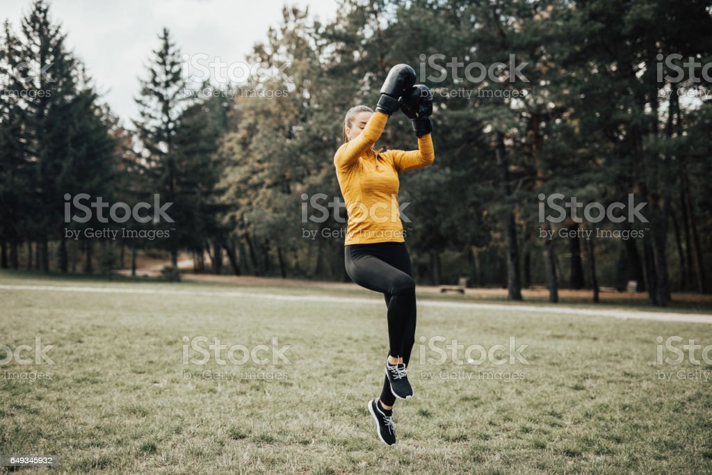 Fit woman kickboxer doing flying knee kick stock photo