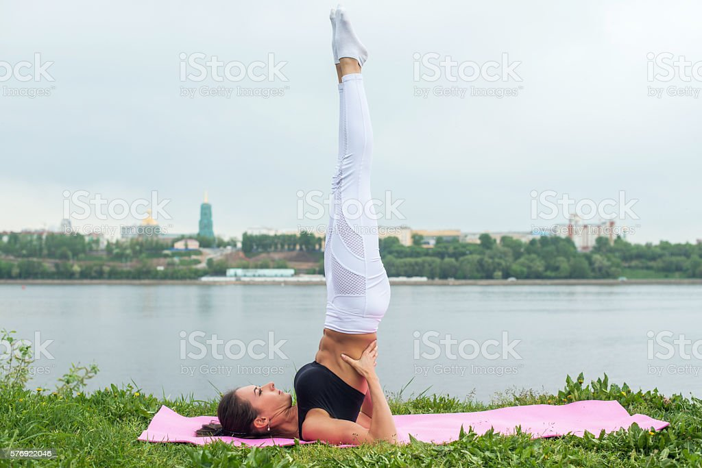 Fit woman making yoga in shoulderstand pose exercising in nature stock photo